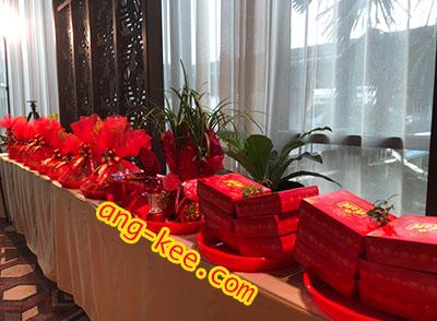 ของหมั้นของฝ่ายหญิง ขนมเปี๊ยะกล่องสีแดง สีมงคลของชาวจีน มีกิ่งทับทิมวางไว้ด้านบน